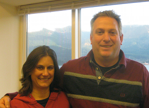 Carrie and Bruce Nissen Pose in their facility with the Columbia gorge views in the background