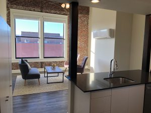 Federal Street Loft apartment living room with exposed brick wall and restored double-pane windows.