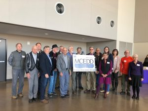 Board members gather around MCEDD sign