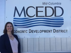 Smiling woman standing in front of sign that reads MCEDD