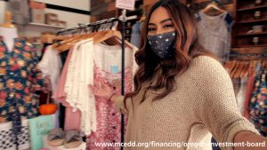 A woman in a face covering stands in front of a clothing rack holding open a door into a shop.