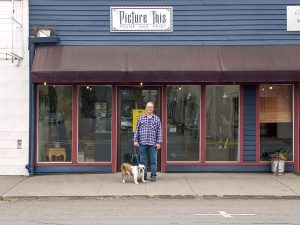 """A man in a flannel shirt stands with his dog in front of a store front with the sign """"Picture This Frame and Print"""""""